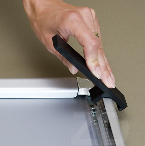Opening of Poster Frame - Security with an opener tool.